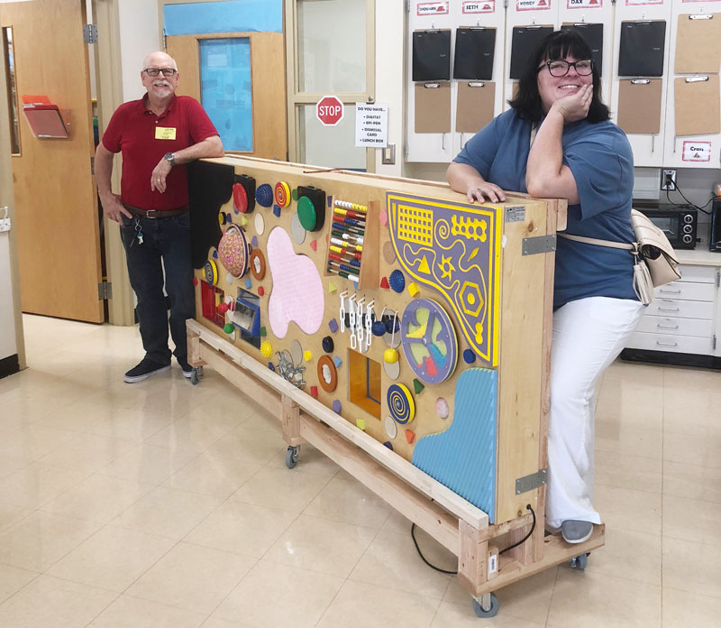 Volunteer David Durbin delivers the multisensory board with the rolling stand that he built for Mrs. Wilson's Washington Center class.