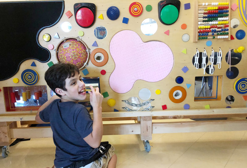 Washington Center student Seth Cedillo enjoys using the class sensory board during leisure time thanks to the rolling stand created by volunteer David Durbin.