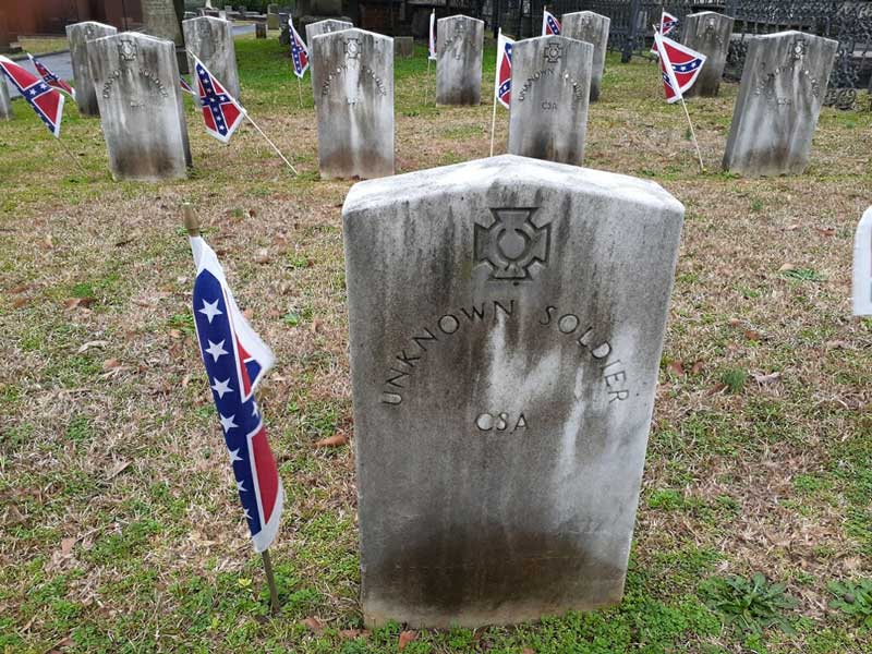 Confederate flags stand sentinel beside graves of Confederate veterans interred in Springwood Cemetery.