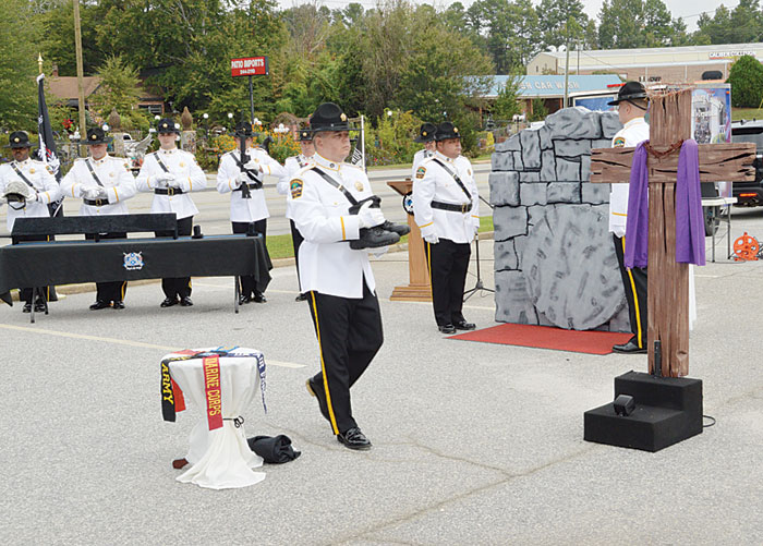 This Ceremony is in honor of a fallen soldier.  The soldier's unpolished boots are carried by an  Honor Guard member to be placed on the wooden block in front of the cross.