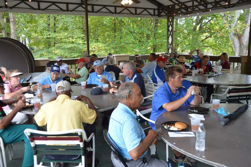 After the tournament, golfers enjoy a meal.