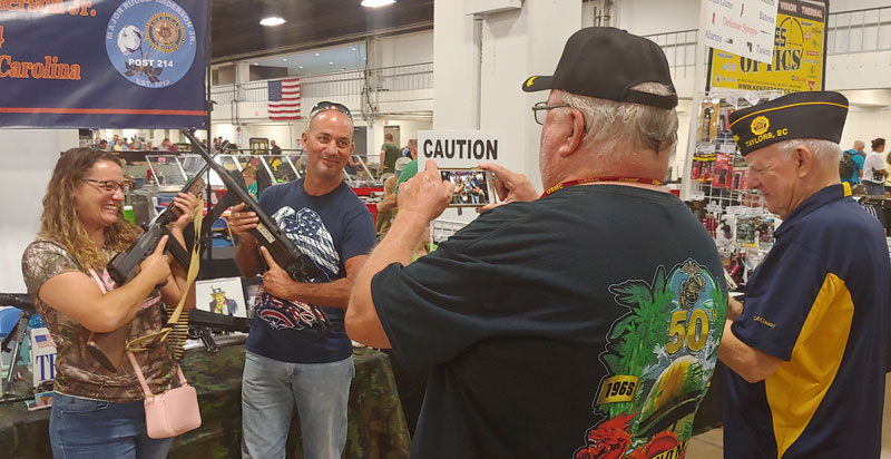 Major Rudolf Anderson, Jr. Post 214 Sergeant-at-Arms Ed Collins and Commander Jack Dorn. Photographed visitors tot he American Legion table at August Gun Show. Holding weapons from the Cecil D. Buchanan Museum of Military History.