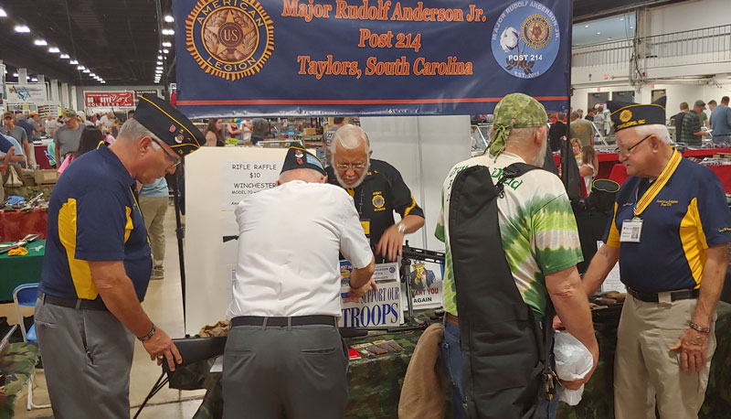 Members of American Legion Major Rudolf Anderson, Jr. Post 214 greet visitors to the August Gun Show. They were informing other veterans know how the American Legion can help them in their civilian life and about the camaraderie of the Legion. Pictured: 2nd Vice Commander John Banning, back to camera Commander Jack Dorn. In blue shirt Museum Director Peter Butchart.