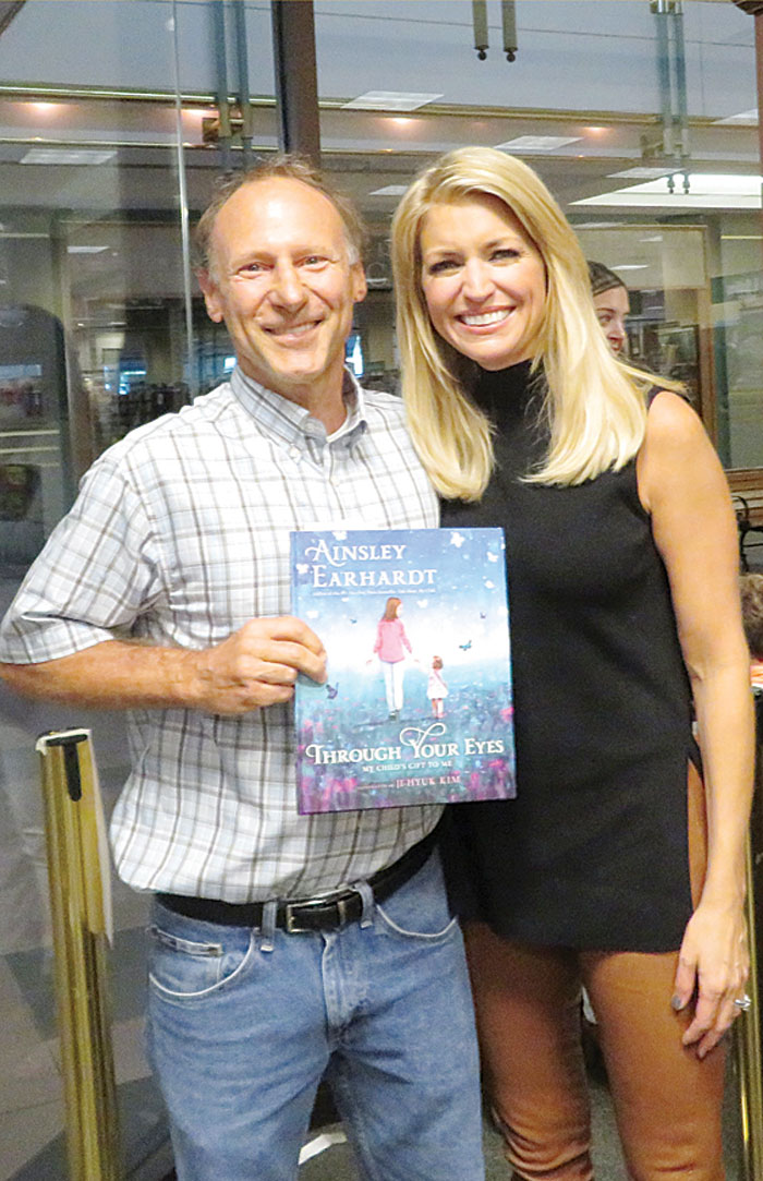 "Jeff West, with Ainsley Earhardt, holding her book ""Through Your Eyes: My Child's Gift to Me."""
