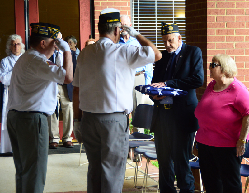 American Legion Post 120 Honor Guard members render a hand-salute at the US Flag that was presented to American Legion Post 3 member Gilbert Scales as his wife Harriette looks on. The US Flag was in honor of US Air Force veteran Frederick Scales who passed on August 2nd, 2018.